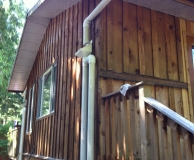 Rain water catchment debris screening and first flush piping. Gabriola Is. BC.